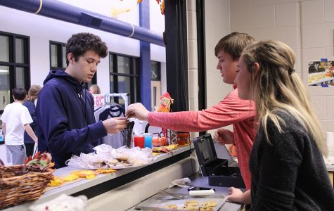 After junior T.J. Smith buys a freshly-baked cookie on Thursday, Nov. 16, senior John States hands back the change.