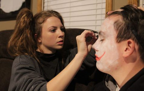 "Putting makeup on senior Garrett Mehner's face, senior Chandler Randolph prepares for the haunted house at senior Preston Cole's house on Monday, Oct. 30. ""To get ready for the [haunted house] we just had to put on our clown makeup on while others had to put on their costumes,"" Mehner said. ""I loved when I sacred this [girl] so bad that she peed her pants."""