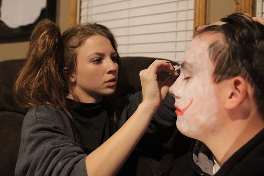 Putting+makeup+on+senior+Garrett+Mehner%27s+face%2C+senior+Chandler+Randolph+prepares+for+the+haunted+house+at+senior+Preston+Cole%E2%80%99s+house+on+Monday%2C+Oct.+30.+%E2%80%9CTo+get+ready+for+the+%5Bhaunted+house%5D+we+just+had+to+put+on+our+clown+makeup+on+while+others+had+to+put+on+their+costumes%2C%E2%80%9D+Mehner+said.+%E2%80%9CI+loved+when+I+sacred+this+%5Bgirl%5D+so+bad+that+she+peed+her+pants.%E2%80%9D