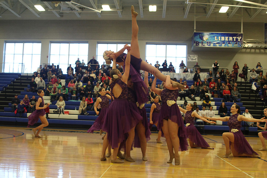 As+junior+Bella+Line+stretches+her+legs+upward+during+the+jazz+routine%2C+other+dancers+focus+on+her+balance.
