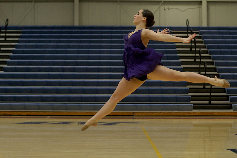 Leaping+off+the+gym+floor%2C+junior+Olivia+Augustine+prepares+to+finish+her+solo.