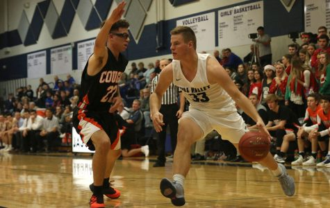 Dribbling the ball, senior Brody Flaming looks for an open path around his defender. The Jaguars were defeated by the Shawnee Mission Northwest Cougars 60-46 on Friday, Dec. 1.