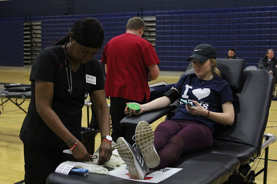 Watching the nurse prep her tools, sophomore Abbie Morgan patiently waits to have her blood drawn during the StuCo-run blood drive on Saturday, Jan. 6.