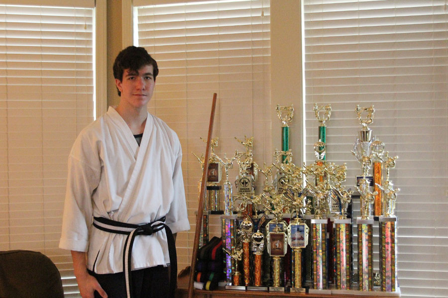 Wearing his black belt, sophomore Justin Deas stands next to trophies that he has won at numerous competitions.