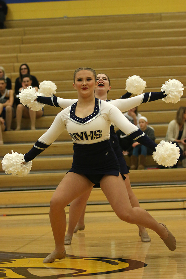 With+arms+outstretched%2C+freshman+Jenna+Haase+performs+the+pom+routine+with+senior+Emma+Barge+right+behind+her.