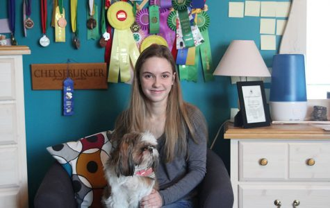 With her dog showing awards behind her, junior Aniston Cumbie sits with her dog Hadie on Monday, Jan. 15.
