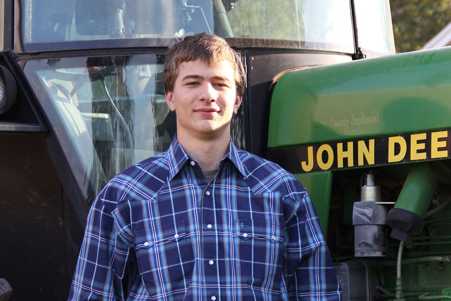 On his family's farm in Arkansas City, Kansas, senior Spencer Rahn stands in front of his tractor.