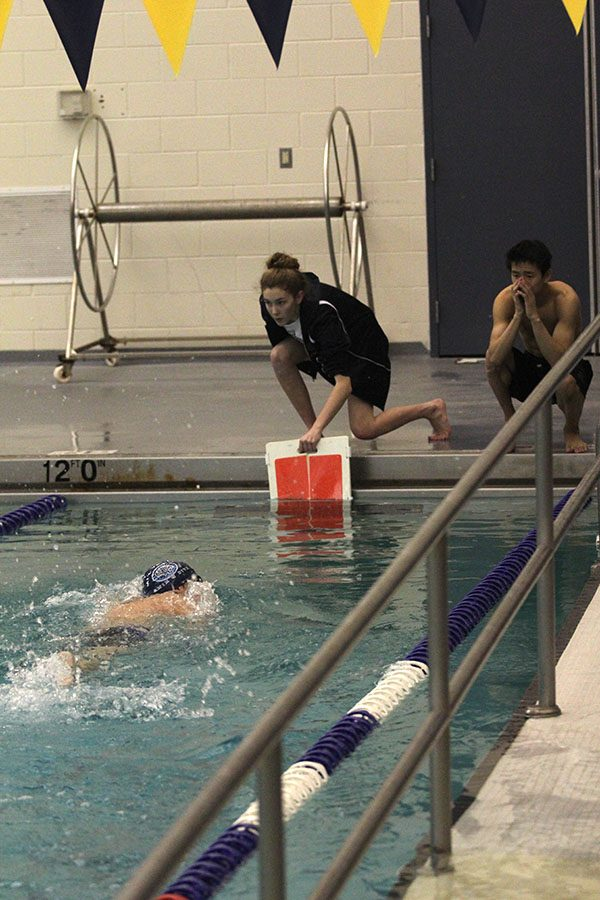 Dunking in a red lap counter to signal the last lap of the 500 free, team manager junior Carly Tribble and sophomore Tyler Draper cheer on freshman Cole McClure.