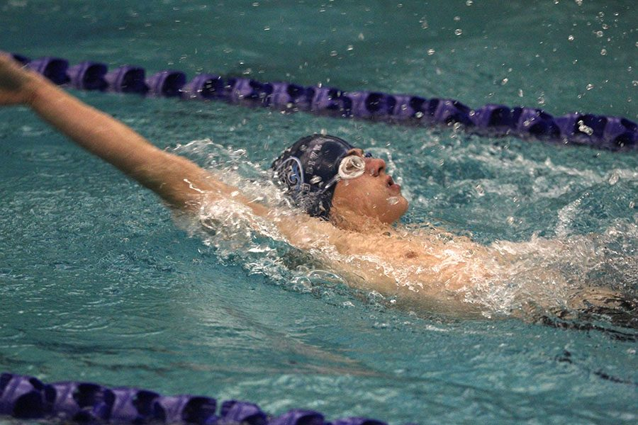 Swimming in the 100 yard back stroke, freshman Noah Collins competes at Chisholm Trail Middle School on Wednesday, Jan. 17.