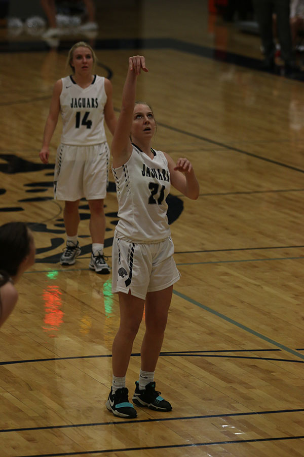 After+shooting+the+ball%2C+junior+Lexi+Ballard+holds+her+hands+up.