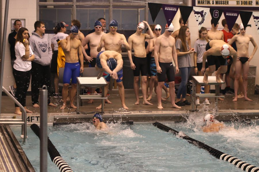 At+the+Eastern+Kansas+League+finals%2C+junior+Chris+Sprenger+completes+his+leg+of+the+200-yard+freestyle+relay%2C+and+junior+Ethan+Forristal+dives+into+the+pool+on+Saturday%2C+Feb.+3.++++++