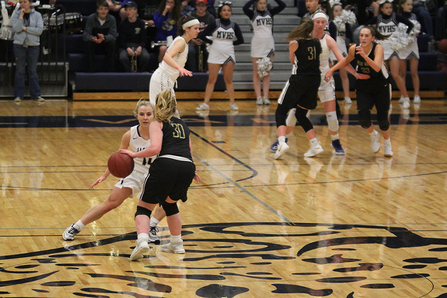 With+a+Blue+Valley+player+approaching%2C+senior+Addie+Hinkle+looks+at+the+ball.++