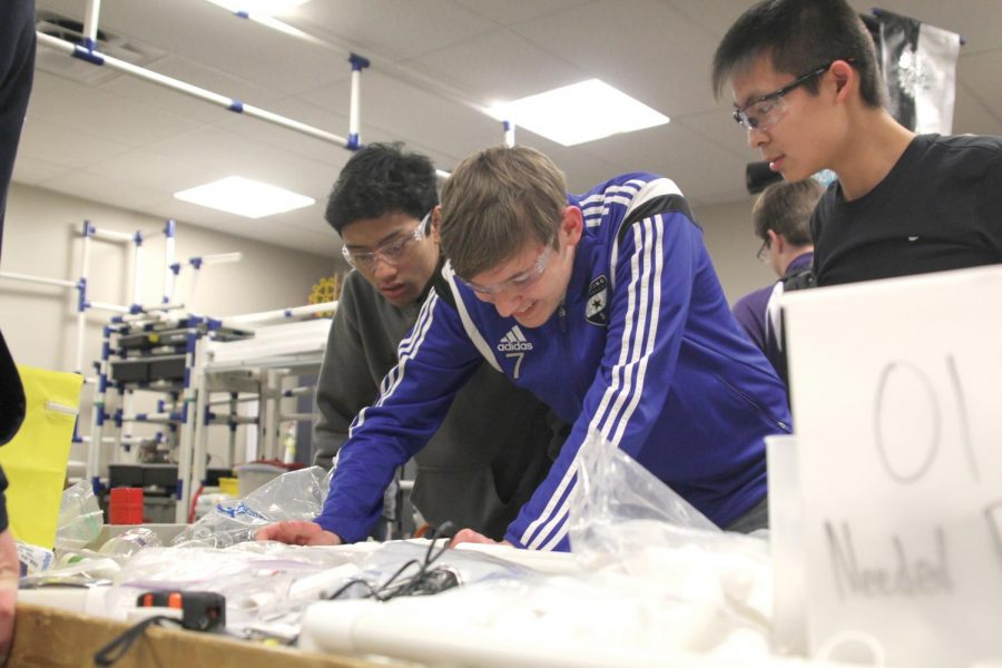 During robotics on Thursday Jan. 18, sophomores Nico Gatapia, Jacob Howe and Kevin Lee work on building a frame for the robot.