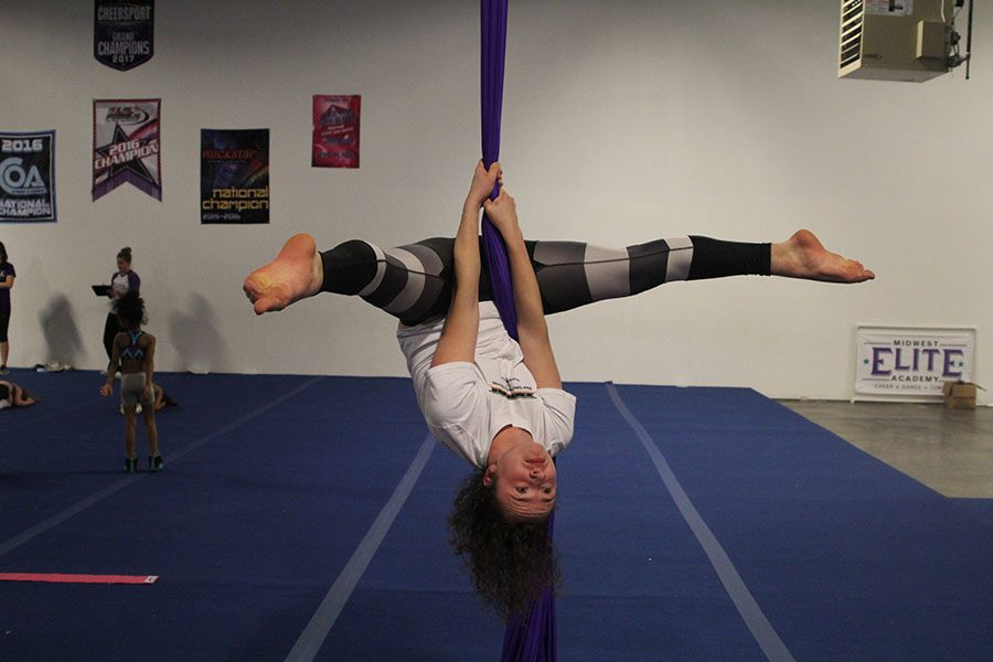 """At Midwest Elite Academy, senior Parker Johnson does a straddle while suspended on aerial silks on Wednesday, Jan. 24. """"It's eerily cool because I have a fear of heights but feel safe in silks,"""" Johnson said."""