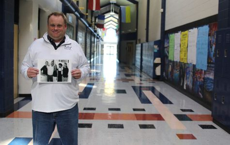 Holding up a photo of former coworkers from his 18 years of experience in the restaurant industry, math teacher Kevin Mosher stands in the main hallway. Mosher worked as a waiter, manager and executive chef before becoming a teacher in 2010.