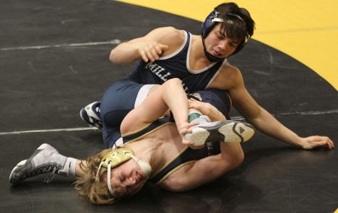 As his opponent struggles under him, senior Bryson Markovich attempts to get a pin.