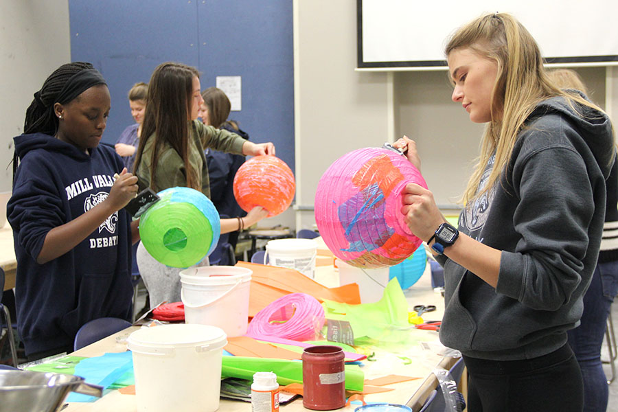 Spreading Mod Podge on a lantern, senior Bella Hadden makes a planet on Sunday, Jan. 28 that will be used for decoration at WOCO.