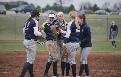 The infield celebrates with each other at their game against the Blue Valley West Jaguars on Tuesday, March 27.