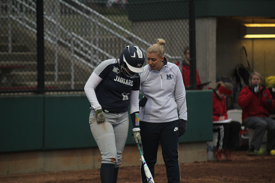 Head+coach+Jessica+DeWild+discusses+some+strategy+with+sophomore+Lauren+Florez+before+she+bats.