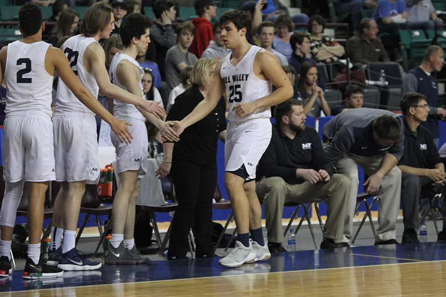 After+coming+off+the+court%2C+senior+Ike+Valencia+high-fives+his+teammates.
