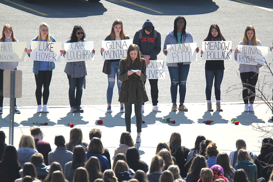 After+people+dropped+their+roses+in+honor+of+the+17+people+who+lost+their+lives+in+the+Parkland+shooting%2C+walkout+organizer+senior+Claire+Boone+reads+a+speech.+