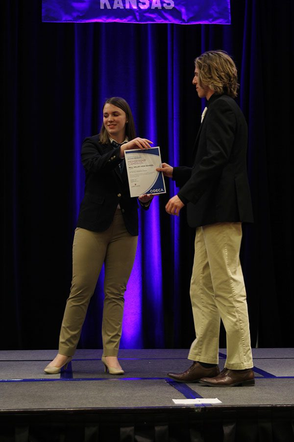 On stage, senior Mitchell Dervin receives a team certificate of achievement award for membership campaign.