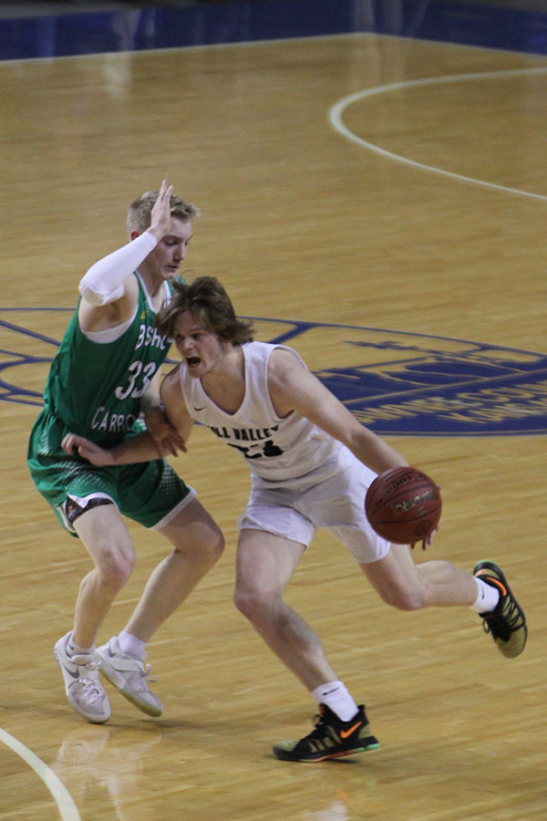 Holding+his+arm+out+to+protect+the+ball%2C+Senior+Cooper+Kaifes+rushes+past+a+Bishop-Carroll+defender.