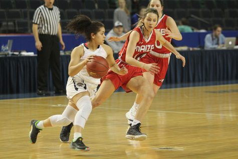 With a defender running alongside her, junior Presley Barton dribbles toward the basket.