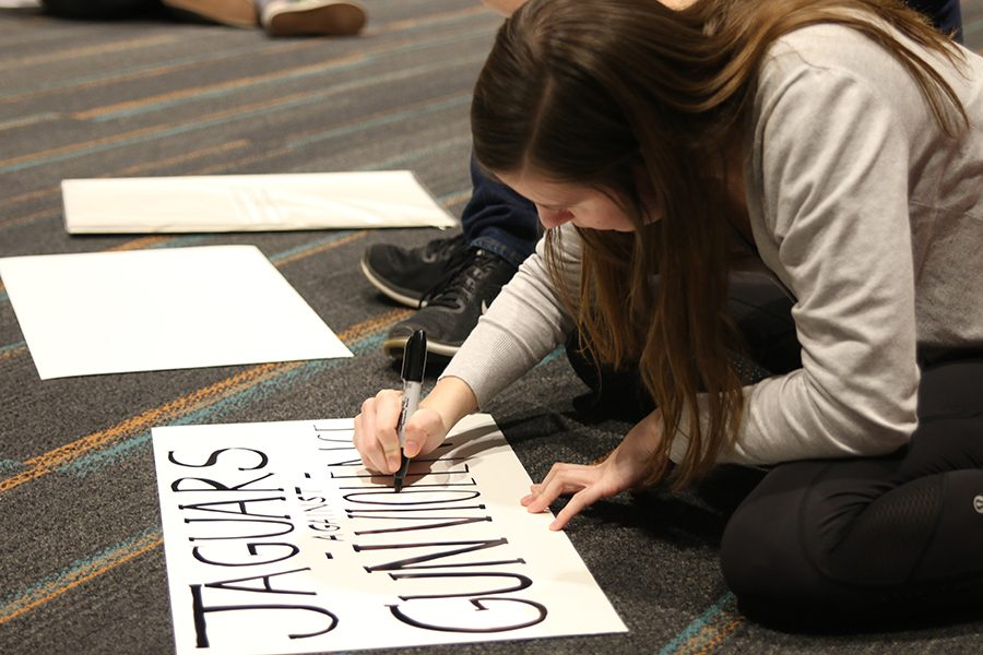 Senior Nora Lucas writes on a poster to be held during the walkout on Monday, March 5.