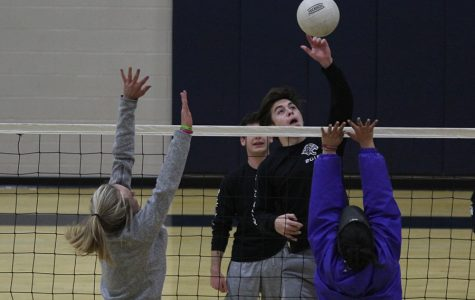 During the Kick Butts volleyball tournament on Wednesday, March 21, senior Brent Stevenson tips the ball over the net as girls from the opposing team attempt to block it. Stevenson's team