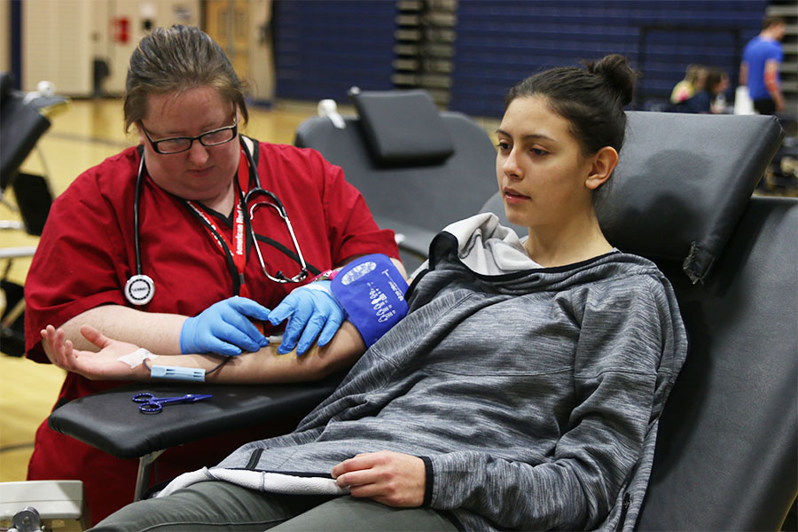 After donating a pint of blood, sophomore Stephanie Madrigal waits for the Red Cross nurse to remove the needle on Thursday, March 22.