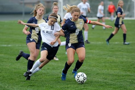 Racing towards the ball, senior Payge Bush battles with an Aquinas midfielder in Mill Valley