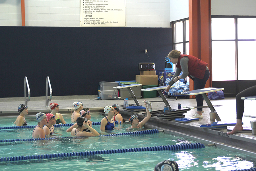 Pointing down towards the pool, head coach Kelly Downward talks to swimmers during practice on Thursday, March 8.