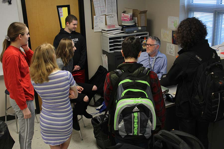 Crowded around science teacher Chad Brown's desk on Tuesday, April 10, students utilize their free time before school to hang out together.