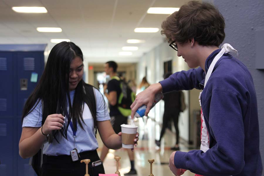 In the main foyer before class on  Friday, April 13, senior Brady Watkins works for the Catty Shack and squirts whipped cream on junior Ally Nguyen's coffee.