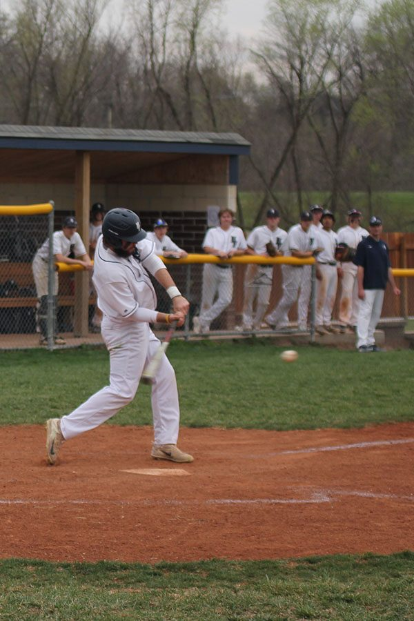 As his team cheers him on, junior Ethan Keopke hits the ball into the outfield.