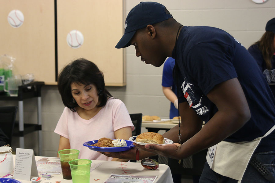 With+business+teacher+Patricia+Brock+watching%2C+senior+Malik+Redmond+serves+her+her+meal.+