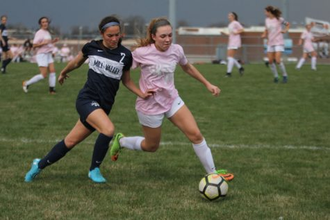 Trying to reach the ball, freshman Peyton Wagoner outruns a SMNorthwest opponent on Friday, April 13. Despite a rain delay, the team won 2-1 against SMNorthwest.