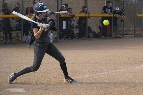 As the pitch comes in, junior Grace Lovett hits the ball.