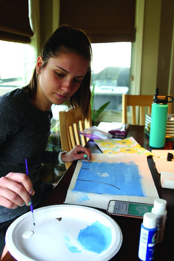 After looking for inspiration on Pinterest, senior Hailey Stelle reaches for more paint on Saturday, March 31.
