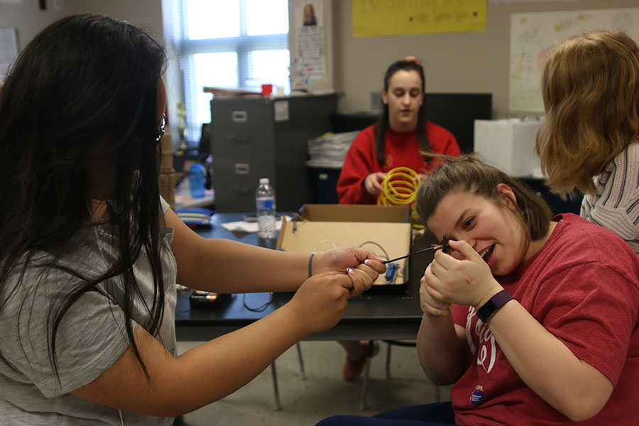 In efforts to expose the copper wire, juniors Crystal Sivilayvong and Lindsey Edwards pull at either ends of electrical wire on Tuesday, April 24.