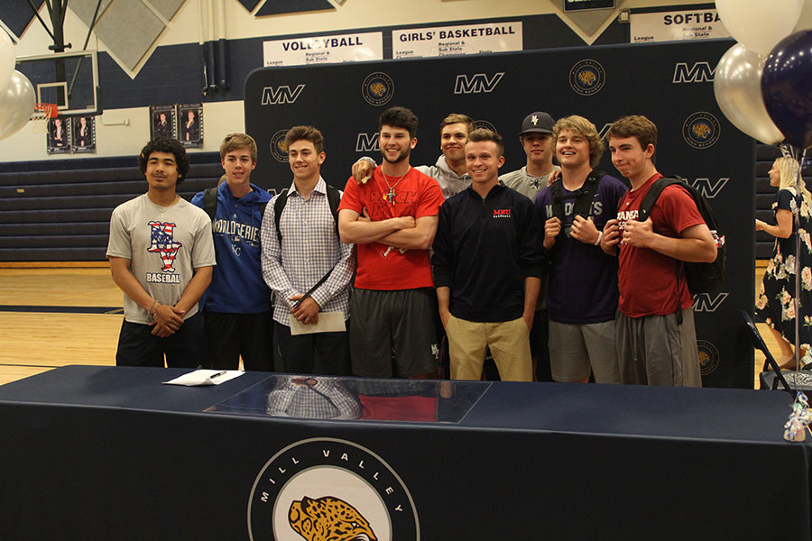 A+group+of+boys+from+the+baseball+team+pose+in+front+of+the+backdrop+after+the+signing+ceremony.