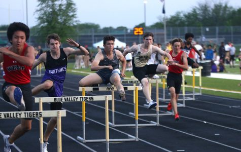 Looking down the track, junior Wyatt Leonard jumps over a hurdle at the EKL league meet on Friday, May 11 at Blue Valley High School.