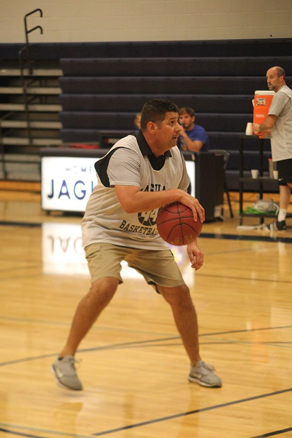 Stepping back from a defender, physical education teacher Travis Keal dribbles the ball.