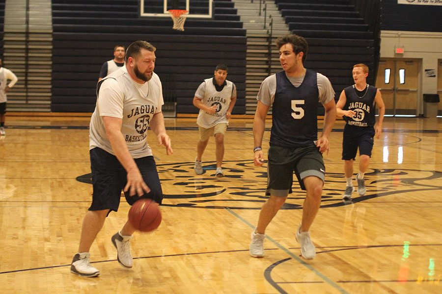 Quickly running back for defense, senior Ike Valencia attempts to steal the ball from math teacher Alex Houlton.