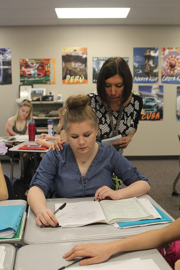 Looking over the shoulder of junior Madelyn Lehn, Spanish teacher Edith Paredes speaks to the class Wednesday, May 2.
