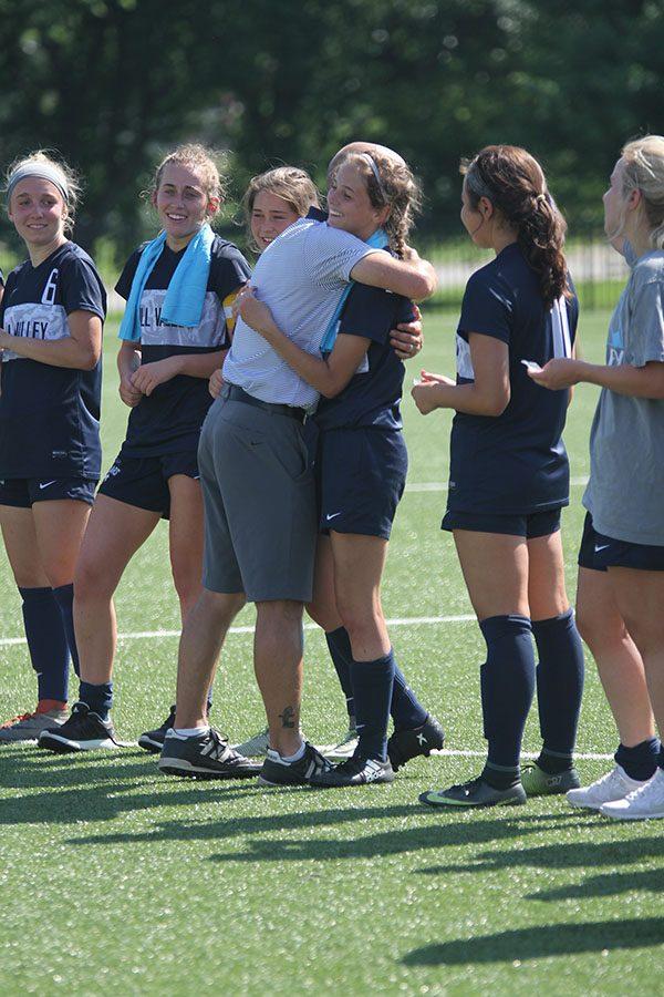 During the awards ceremony, senior Payge Bush hugs head coach Arlan Vomhof.