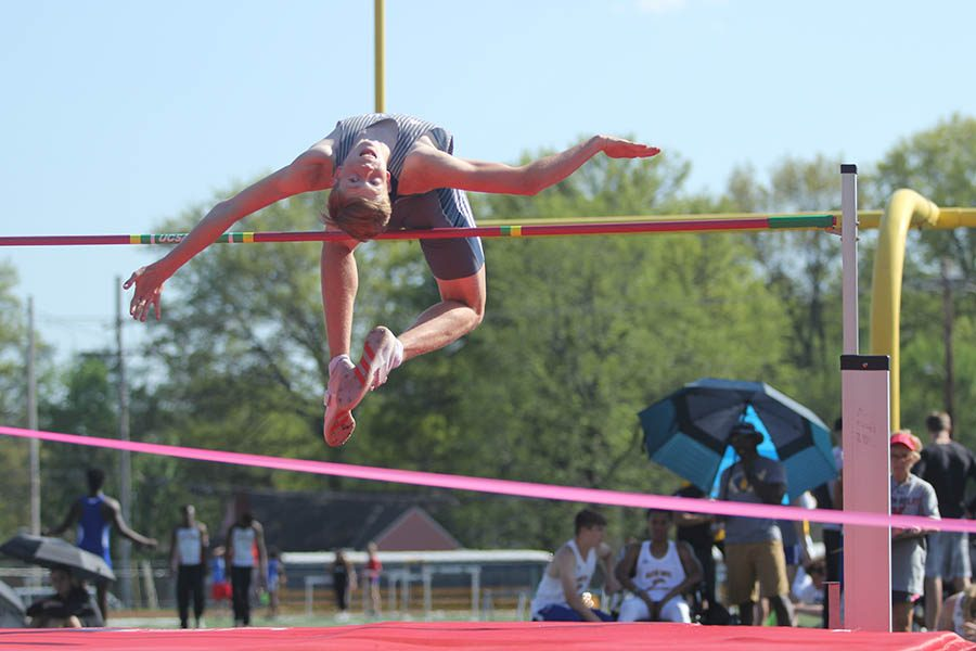 At the annual Shawnee Mission North relay, junior Harry Ahrenholtz maneuvers over the high jump bar. The team competed against 36 other schools during the relay.