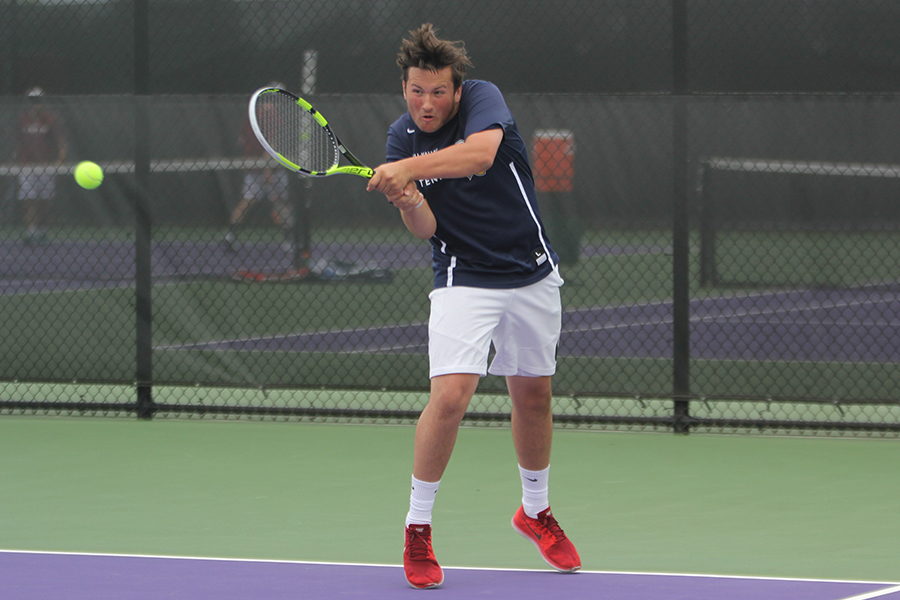 Competing+in+his+first+set+of+doubles%2C+junior+Jacob+Hoffman+does+a+two-handed+backhand+swing.