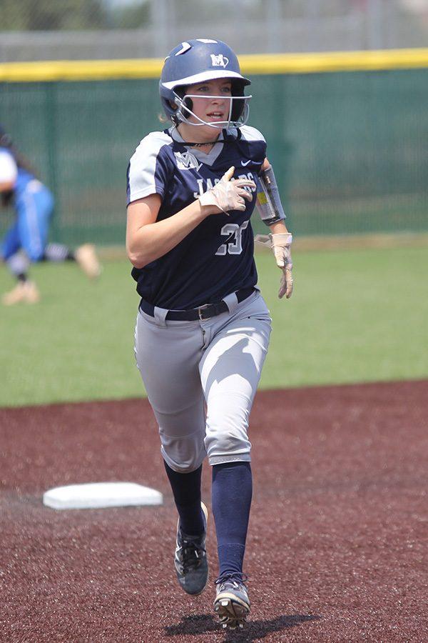 Keeping her eye on members of the opposing team, junior Grace Lovett prepares to run into third base.
